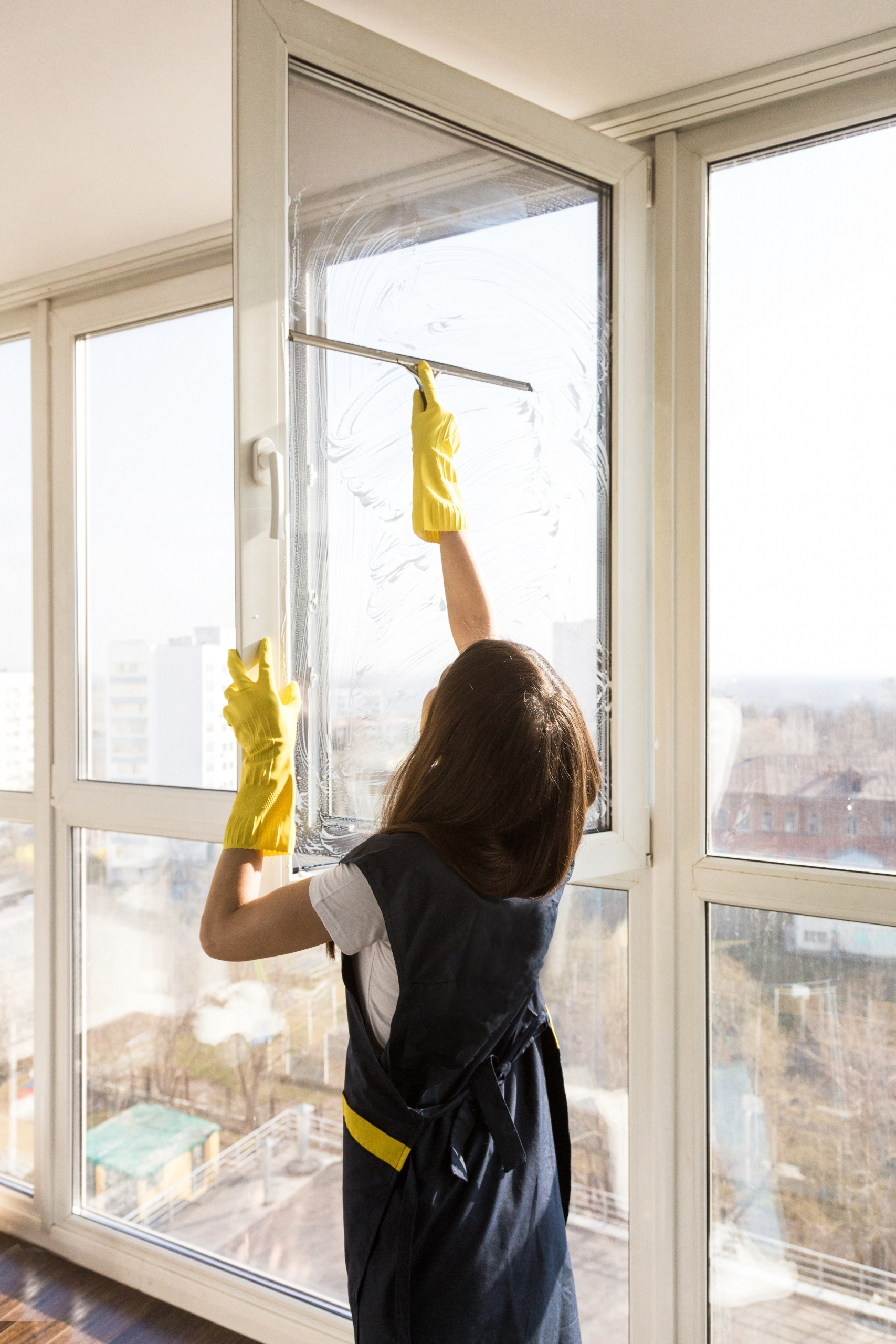 woman in uniform and yellow gloves washes a windows with window scraper